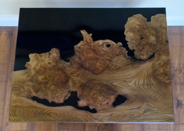Burr elm coffee table surrounded by a black sea of epoxy resin