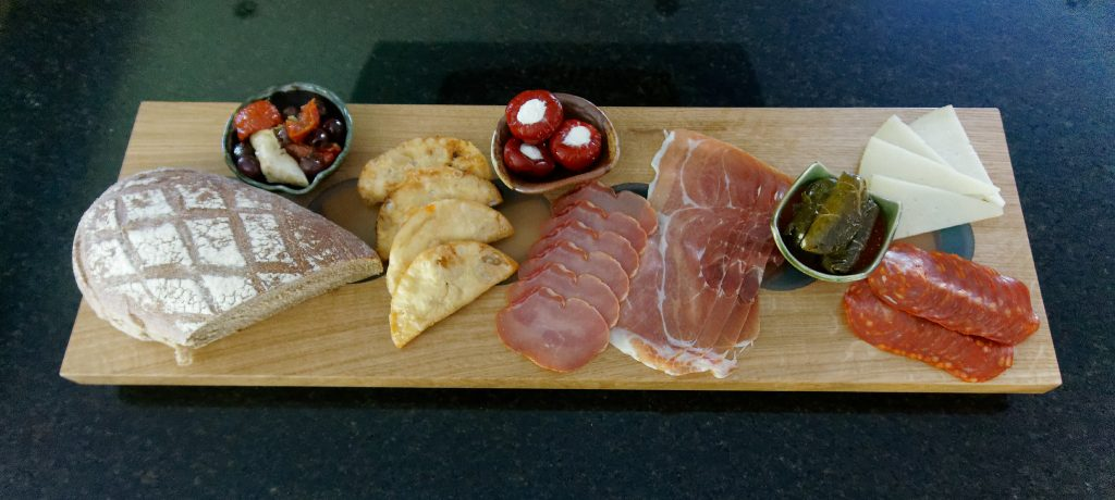Oak Charcuterie Board with selection of cold meets and side dishes