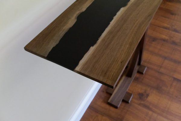 Slim tall live edge walnut console table showing grain and black resin
