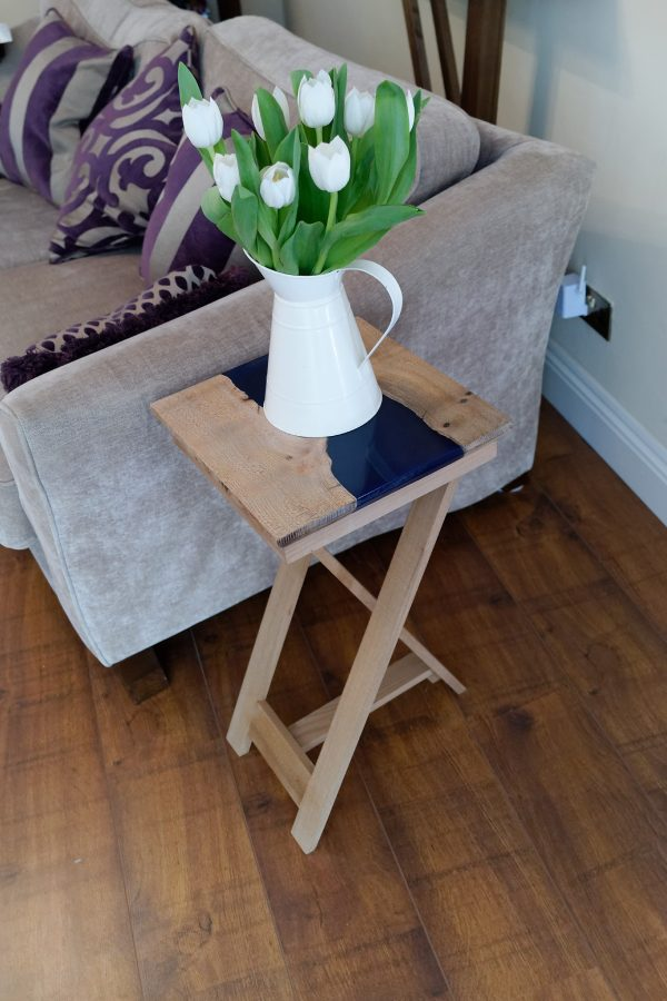 Ash and blue resin side table on tripod legs with vase of flowers