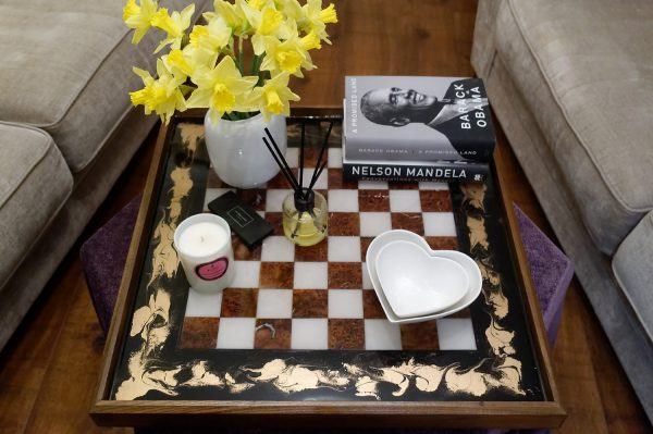 Close Up of Chess Board Ottoman Tray Dressed with Accessories and Books